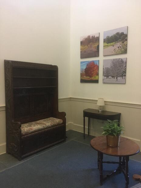 image of Reception with carved chair and four pieces of artwork depicting the four seasons.